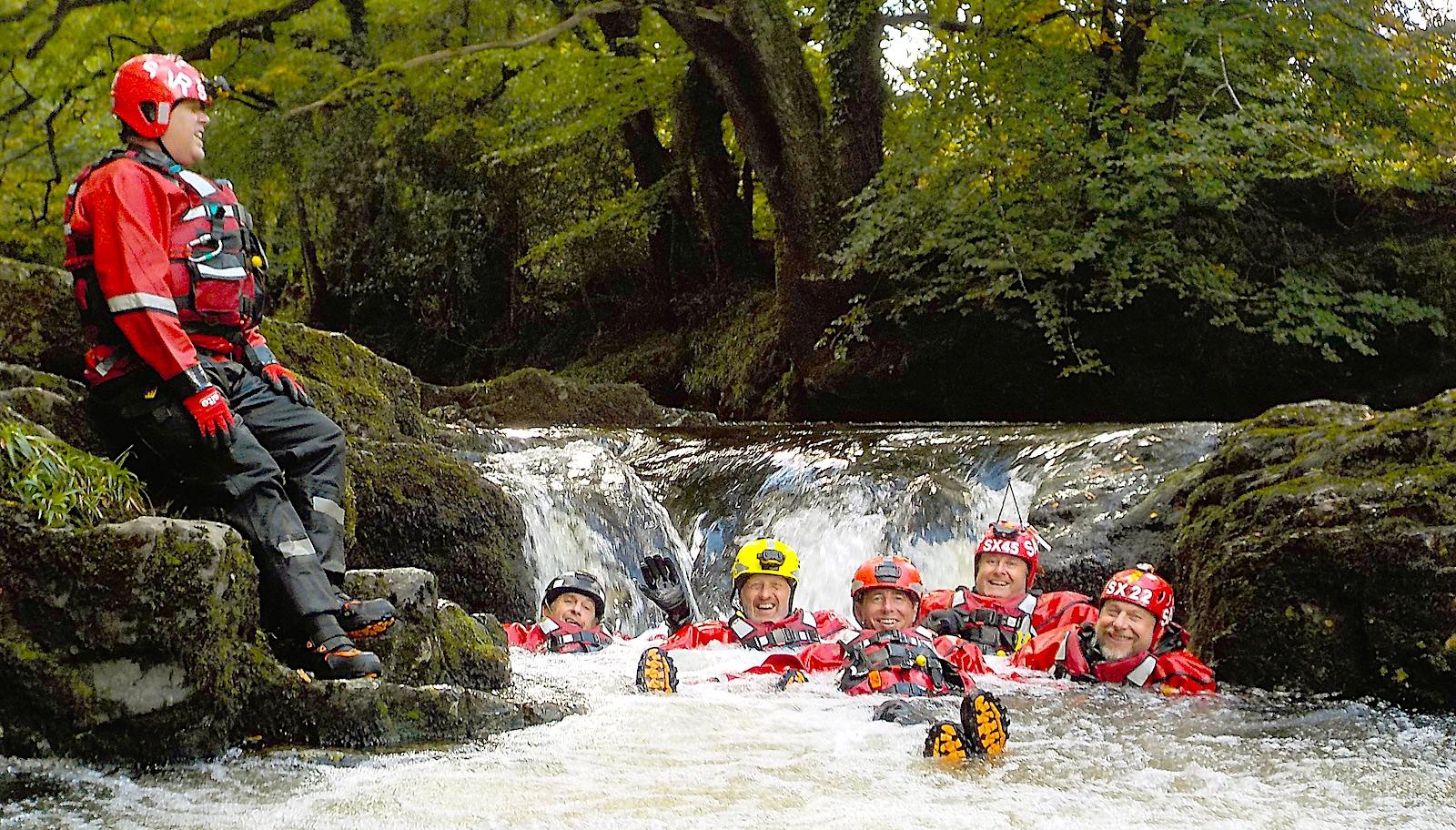 The water team sitting below a waterfall